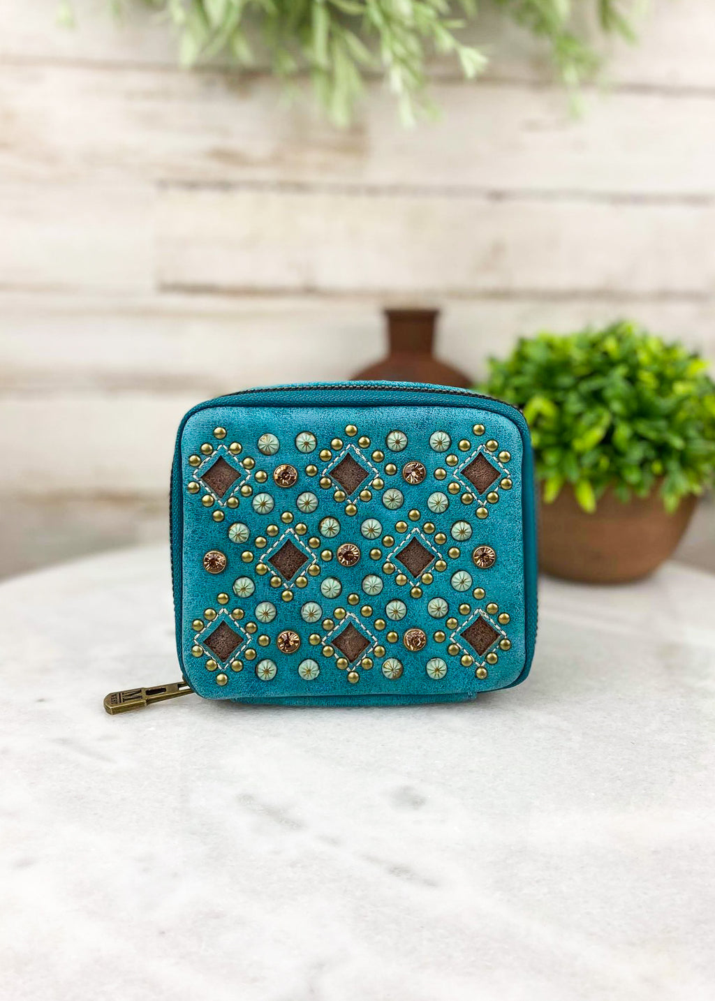 Small turquoise and antique studded pill and accessory travel case with zip around closure and plain turquoise leather on back taken inside on white table with green floral décor