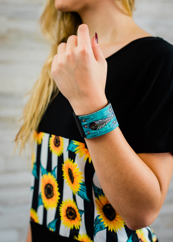 Black leather cuff with turquoise feather design on blonde model