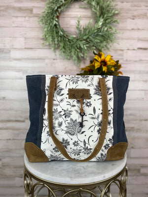Front View of Vintage Ivory Floral Tote Handbag With Brown Leather Shoulder Straps and Black Key and String Detail, Blue Canvas Sides, Brown Leather Detail at the Bottom, On White Table Taken Inside with Studio Lights and Floral Accents