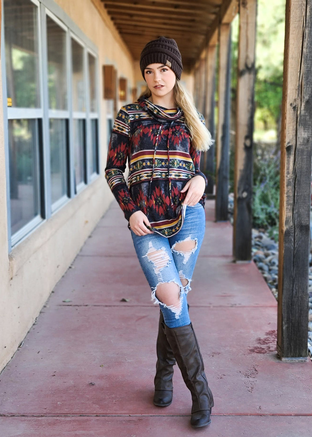 Black Multi Color Aztec Cowl Neck Long Sleeve Top on blonde model with brown beanie, distressed denim jeans and brown tall boots