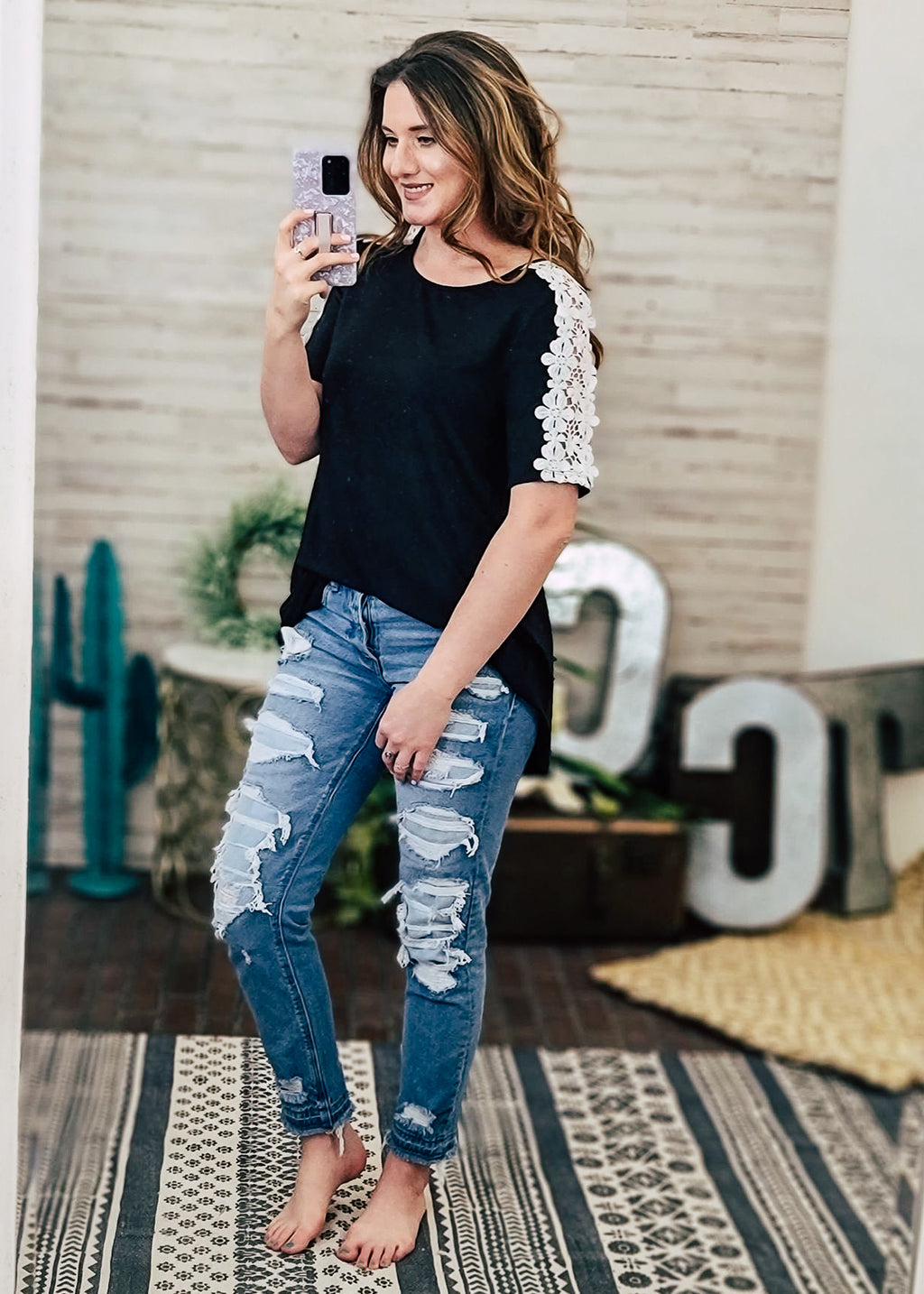 Black Floral Crochet Tunic Top on model with distressed jeans