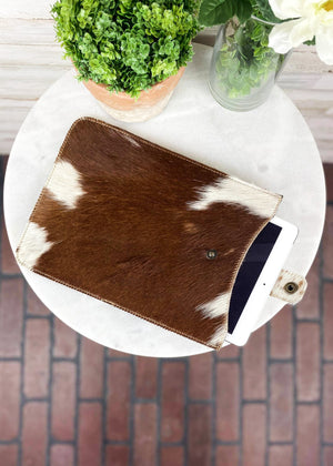 Brown & White Cowhide Tablet Sleeve with tablet tucked inside