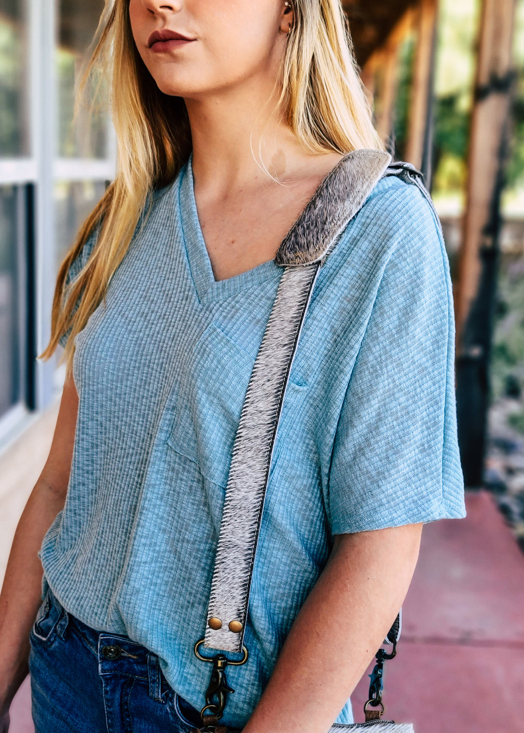 Grey Cowhide Purse Strap on model with blue shirt