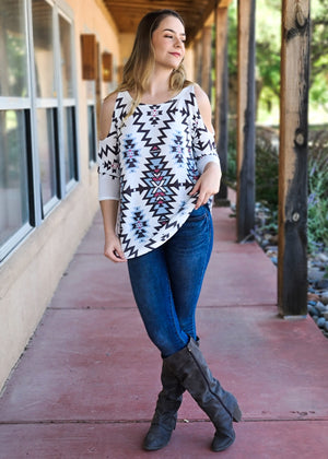 Ivory & Blue Aztec Cold Shoulder Top on blonde model with denim jeans, shot outside