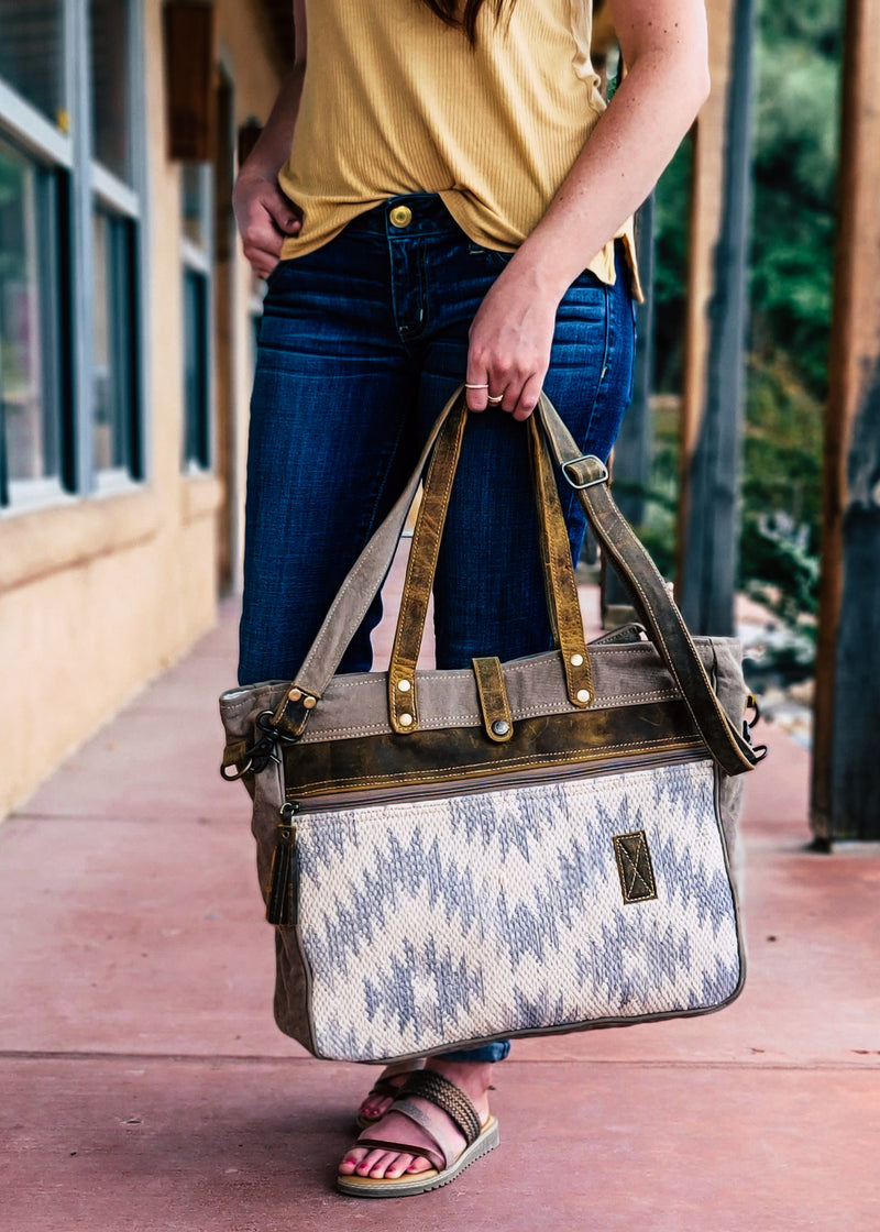 Light Blue & Ivory Aztec Leather Zip Weekender Bag on marble table