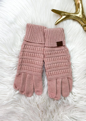 pink knit gloves on white rug