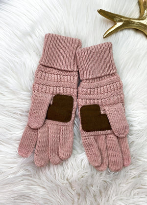 pink knit gloves inside on white rug