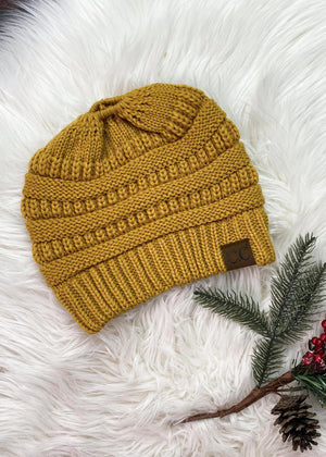 mustard knit beanie on white fur rug with mistletoe prop