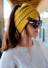 Mustard Ponytail Beanie on brunette model with grey waffle shirt, shot outside