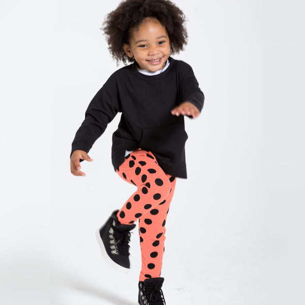 toddler girl in coral jogger sweats with black polka dots