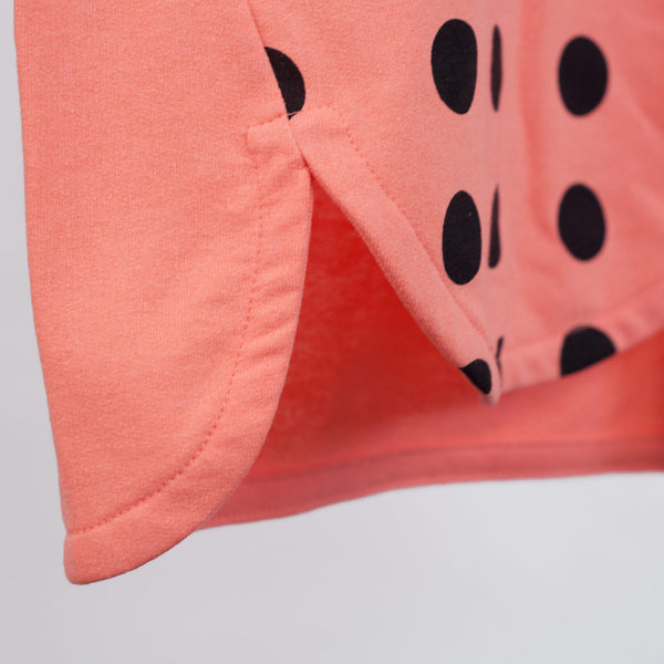 forward side seam detail on kids coral t-shirt dress with black polka dots