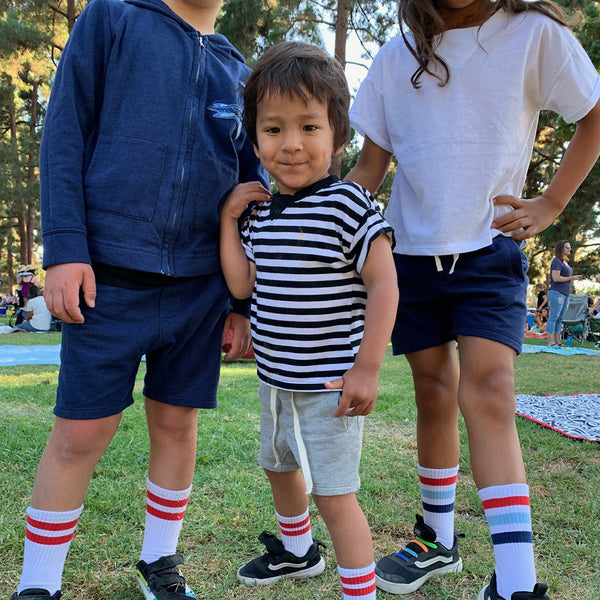 3 kids wearing drawstring sweat shorts with two front pockets in grey and navy blue