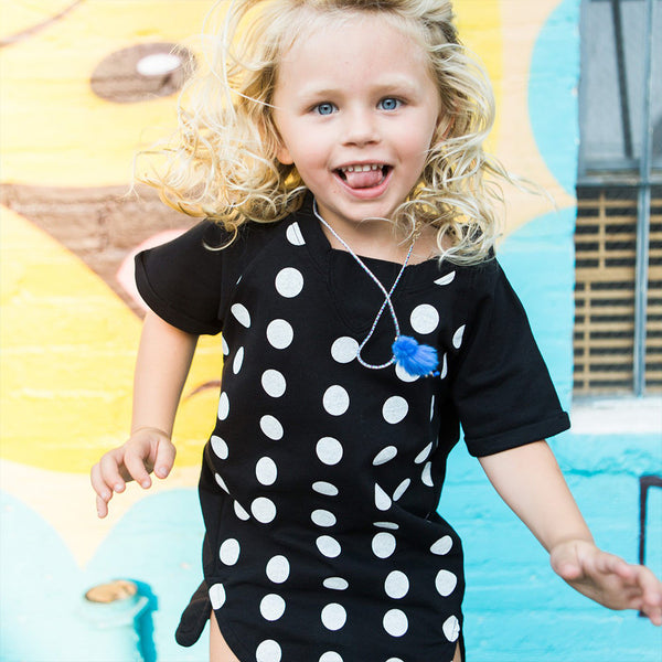 girl in short sleeve black t-shirt dress with white polka dots and curved hem detail