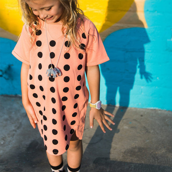 girl in kids short sleeve coral t-shirt dress with black polka dots and curved hem detail