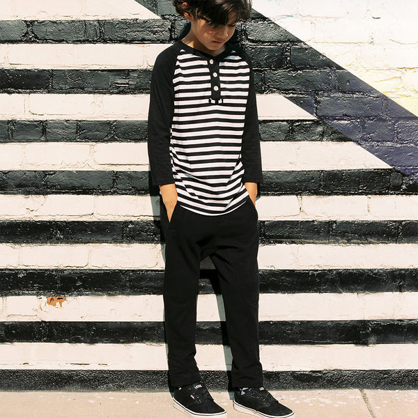 boy in striped raglan tee and slim black joggers