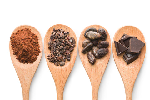 Spoonfuls of Cacao Powder, Cacao Nibs, Chocolate Covered Cacao Beans, and Dark Chocolate Bars