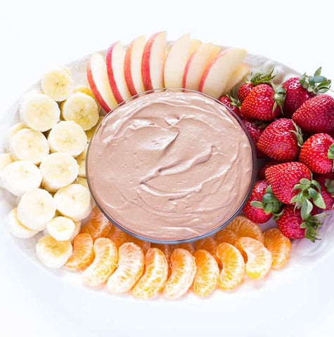 Bowl of almond butter surrounded by fresh fruit pieces