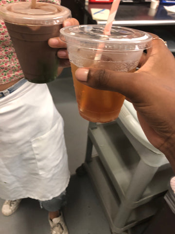 Cups of chocolate drinks in hands being cheersed