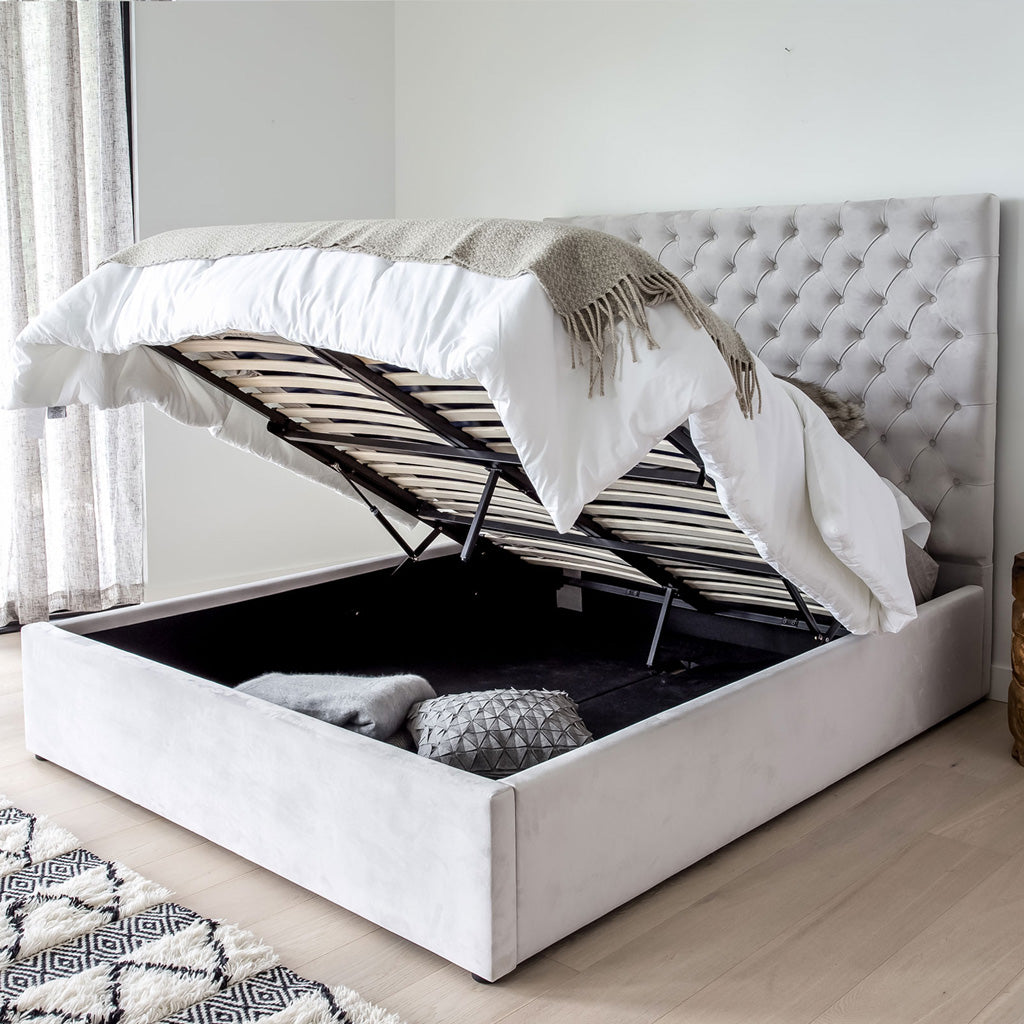 Product image of the Jolie Storage Bed. Shown in light grey. 45 degree side view of staged/dressed bed showing mattress raised and storage area open.