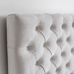 Product image of the Jolie Storage Bed. Shown in light grey. Showing closeup of the headboard, fabric and tufting details.