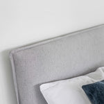Product image of the Julia Storage Bed. Shown in cement. Close up of headboard detail and fabric.