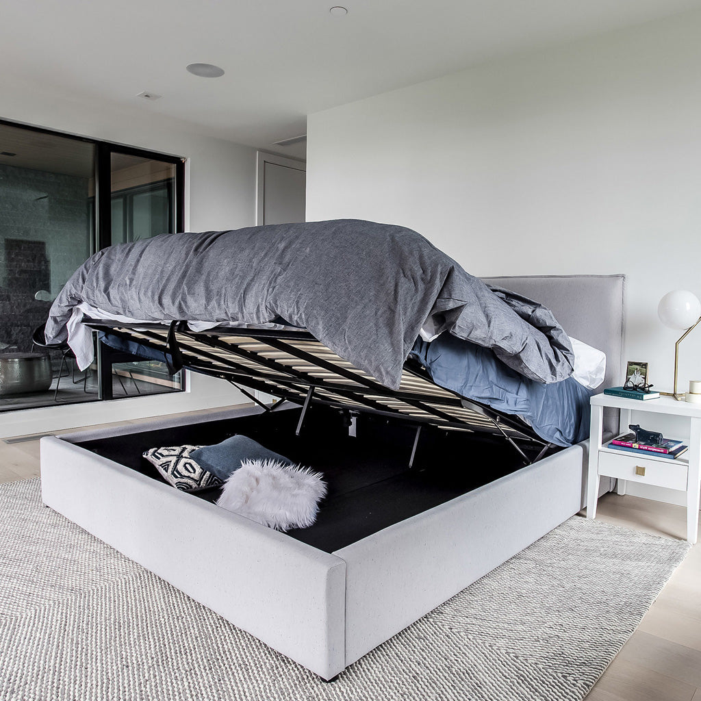 Product image of the Julia Storage Bed. Shown in cement. 45 degree side view showing mattress raised and storage area open.