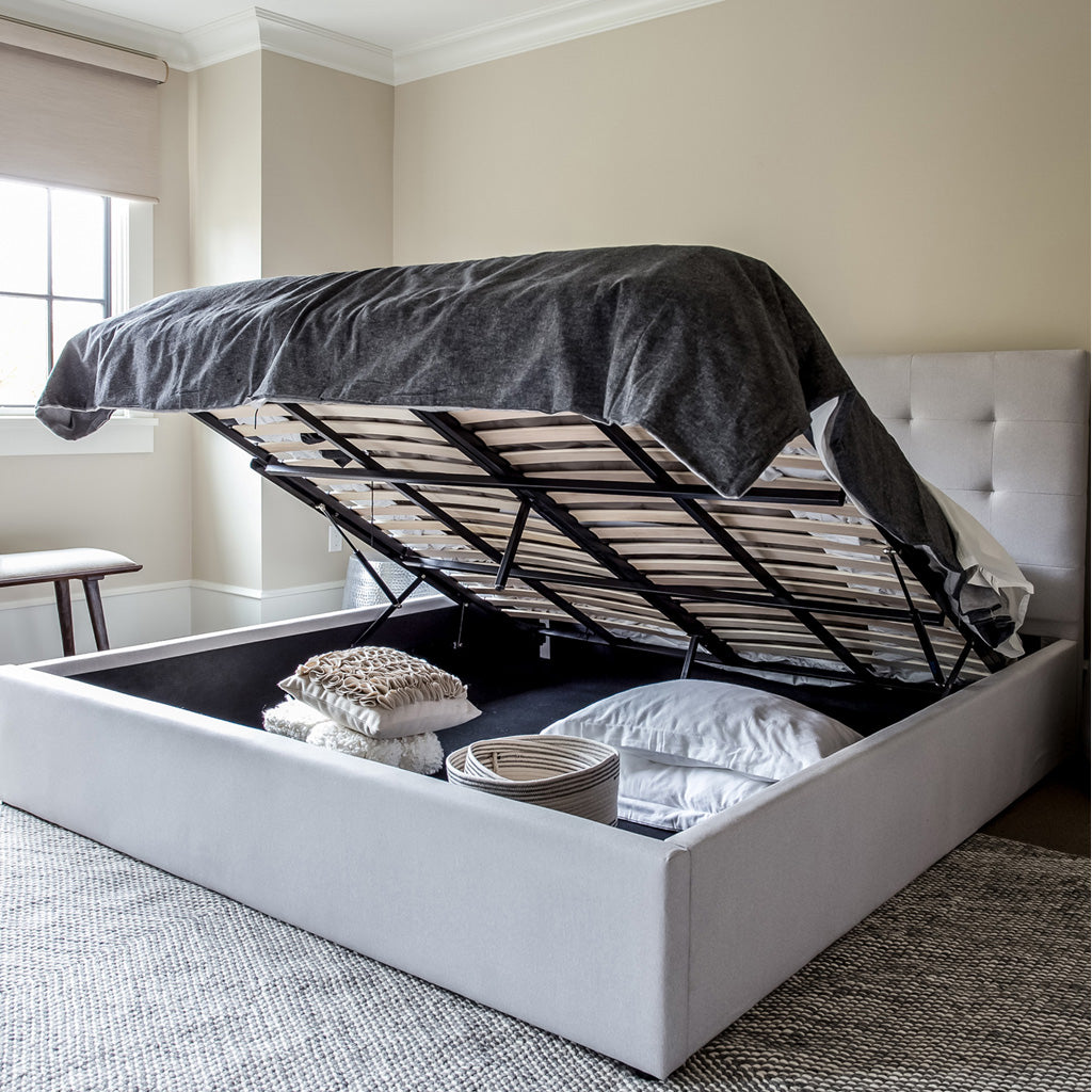 Product image of the June Storage Bed. Shown in horizon grey. 45 degree side view showing mattress raised and storage area open.