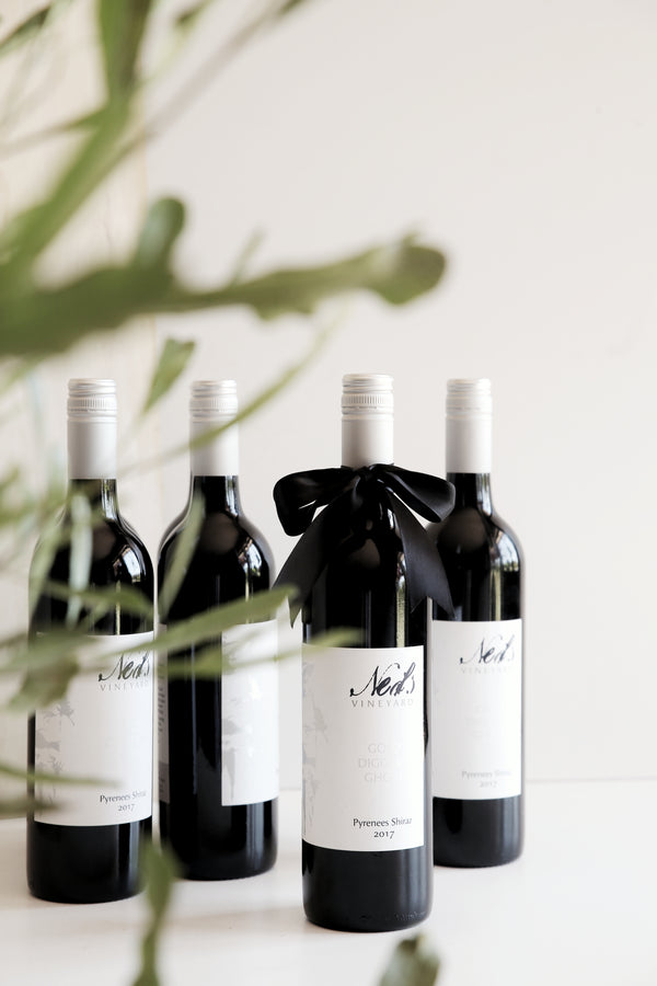 Australian Red Wine bottles of Shiraz standing with eucalyptus leaves in the front. White clean labels with silver branding.