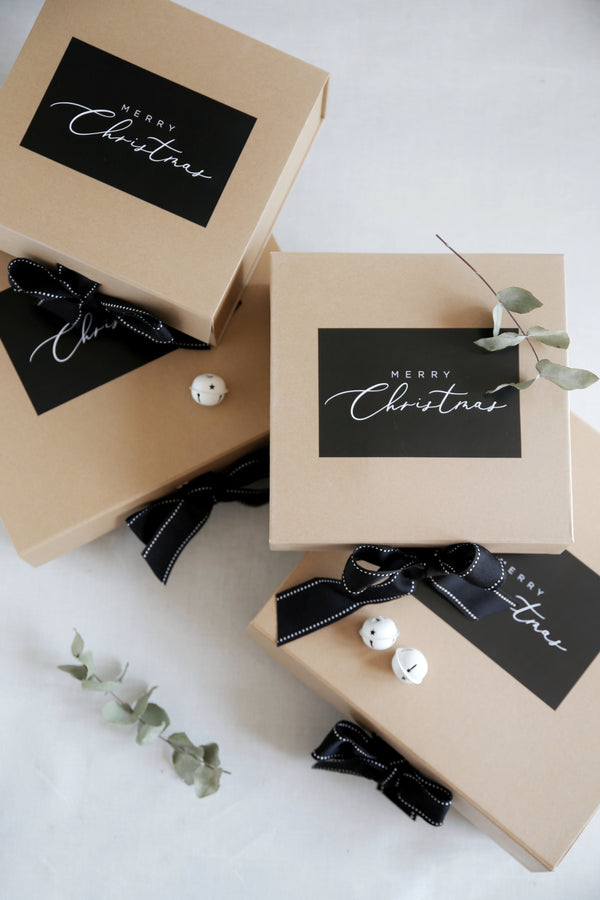 Christmas Hampers say it with a box with black bows and merry Christmas on the top of the box in black and white luxury printing