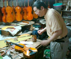 Chinese violin maker working in his shop