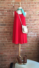 red sleeveless dress, mint kerchief, brown wedges, and cream crossbody