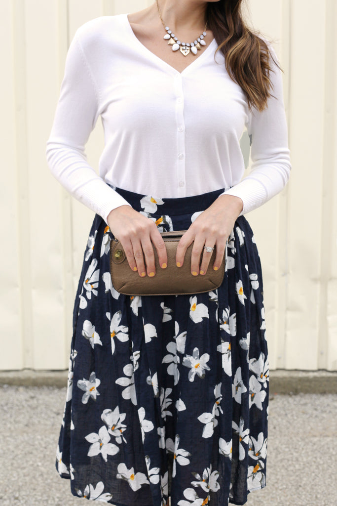 Floral skirt, wristlet, & ivory cardigan close-up