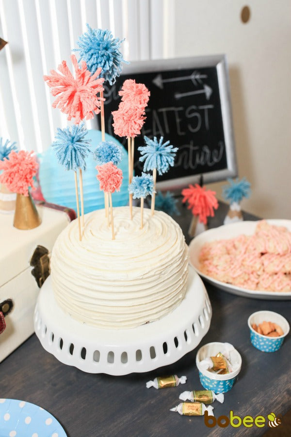 white cake with pink and blue toppers