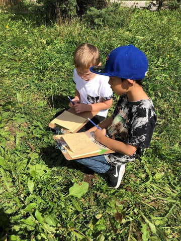 Two boys sit in the green grass with clipboards on their laps as they participate in environmental stewardship programs.