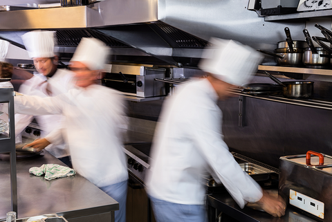 Cooks busily prepare food in a restaurant they're not thinking about water use
