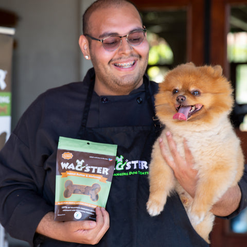 Man holding dog and bag of Wagster dog treats