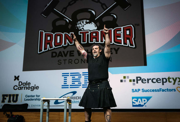 strongman Iron Tamer Dave Whitley performs a feat of strength on stage