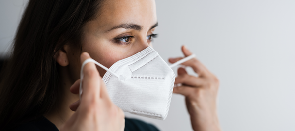 Woman putting on N95 mask