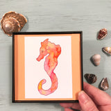 """Orange Gelato Seahorse"" framed with tangerine-colored background"