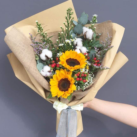 Bouquet of artificial cotton flowers, fresh sunflowers, red berries, white peacocks, baby's breath, purple caspia, and eucalyptus leaves