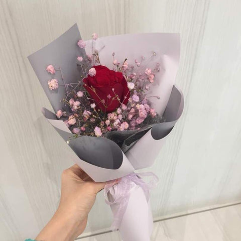 Bouquet of red roses and spray-coloured baby's breath