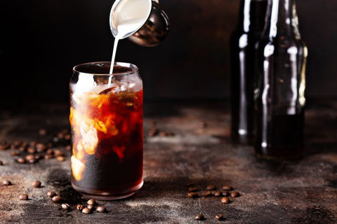 Cream being poured in cold brew coffee