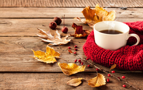 Cup of coffee sitting next to a sweater and fall leaves