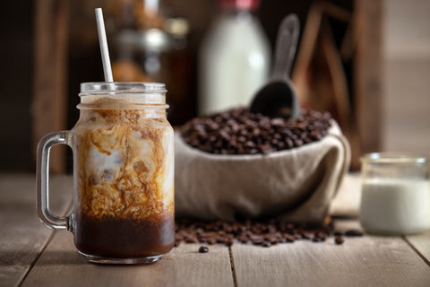 Freshly made iced Mexican mocha sitting next to a bowl of coffee beans and a glass of milk.