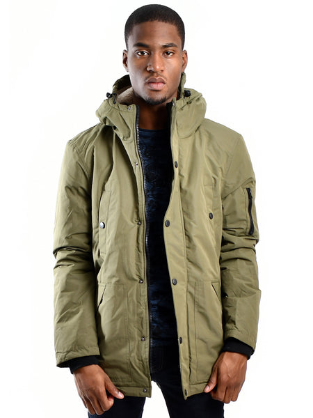 Sherpa lined winter parka with hood from British designer dSTRUCT, offered by Whiskey Ginger. Khaki military green colored fabric. Zippered closure. Front view of parka, worn by a male model.