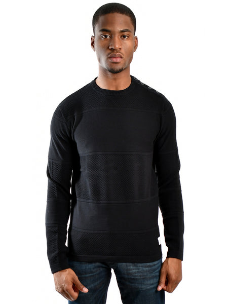 Black crewneck sweater from Danish designer Jack & Jones, offered by Whiskey Ginger. Ribbed and honeycomb alternating knit fabric. Button closure over left shoulder. Front view of sweater worn by a male model.