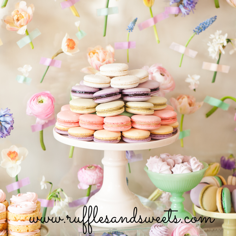 pretty flower backdrop, macarons, milk glass cake stand