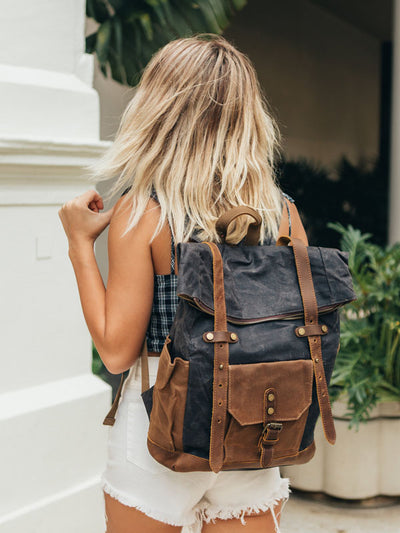Woman wearing grey canvas and leather camera bag backpack