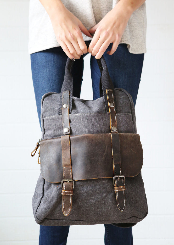 Woman holding grey canvas leather camera bag backpack