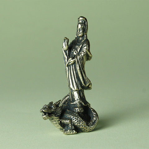 Kuanyin small statue in brass, crossing the 'ocean of suffering' on a dragon. Quan Yin is the Buddhist goddess of compassion.